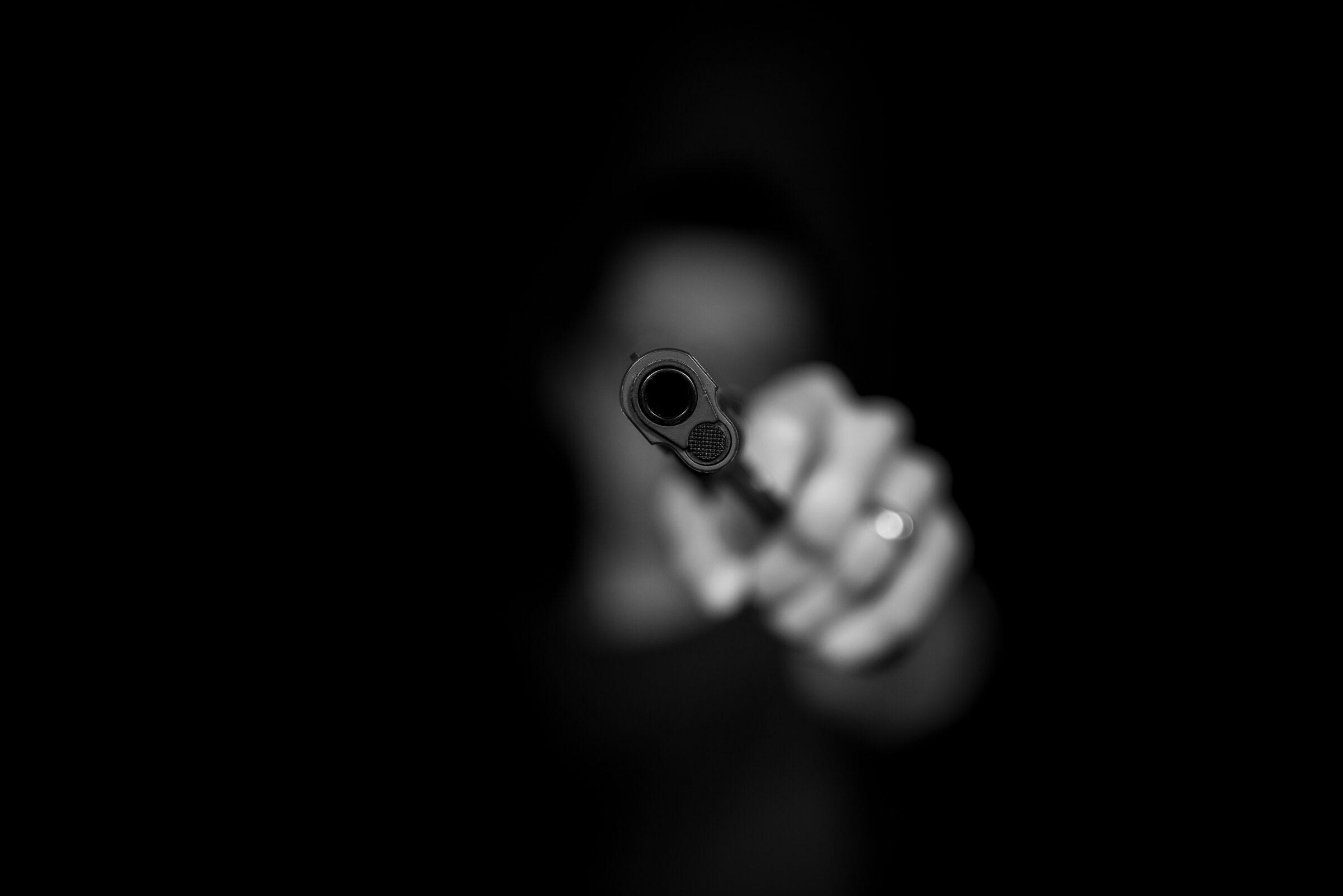 De loop van een wapen vastgehouden door een hand. Vaag op de achtergrond het gezicht. Zwart-wit