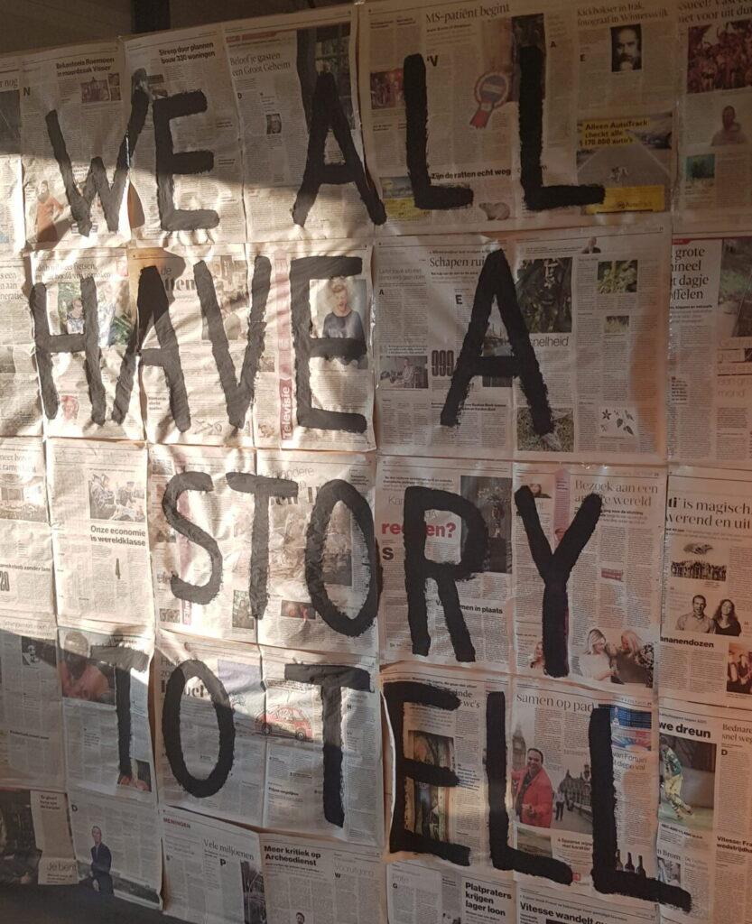 Allemaal kranten op een muur met de tekst we all have a story to tell