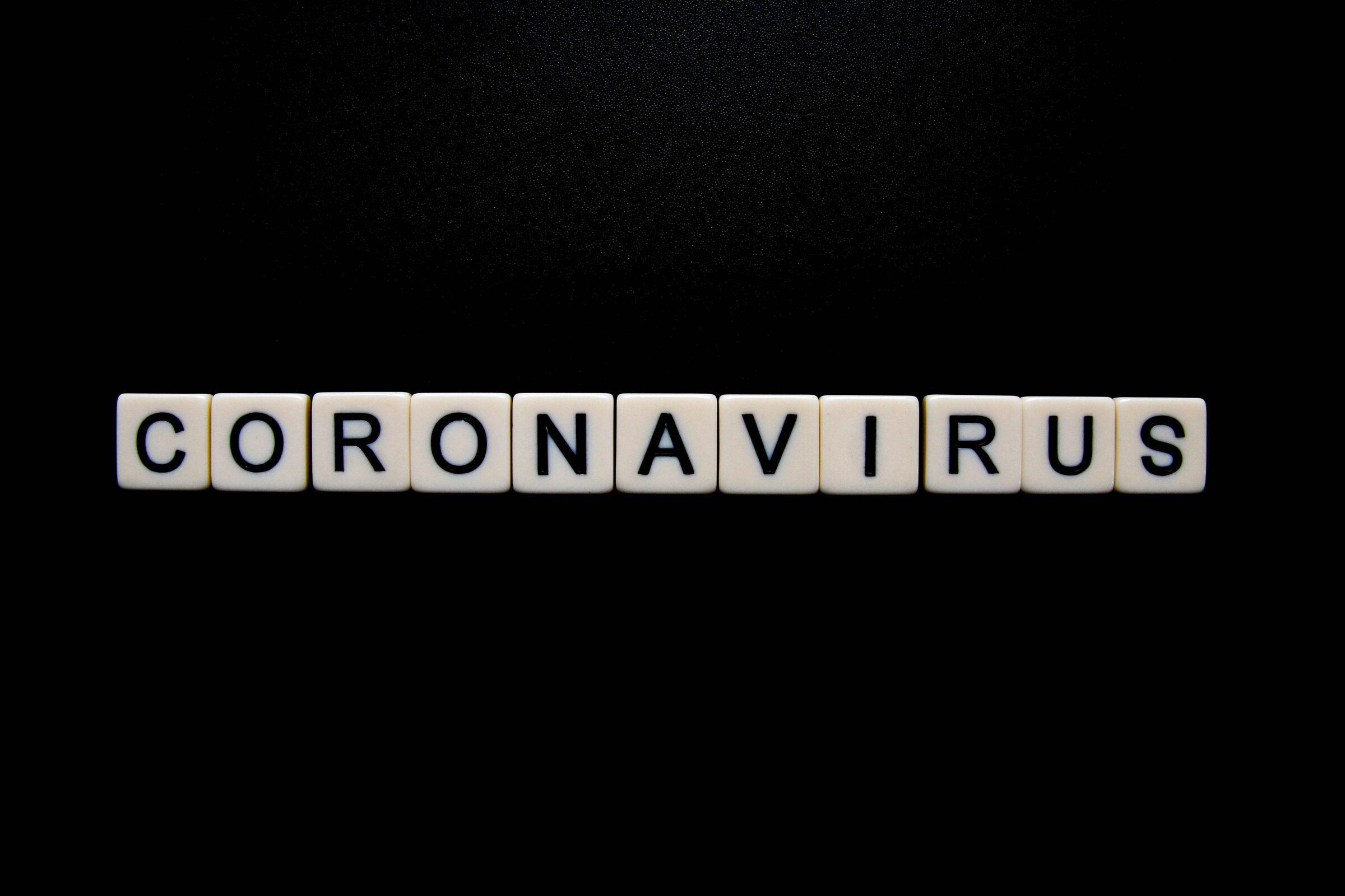 Met scrabble blokjes het woord coronavirus neergelegd op een zwarte achtergrond.