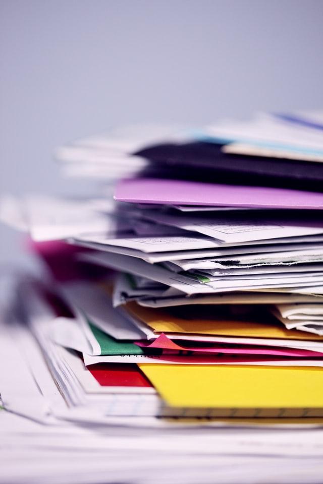 Stapels met post en papieren in verschillende kleuren