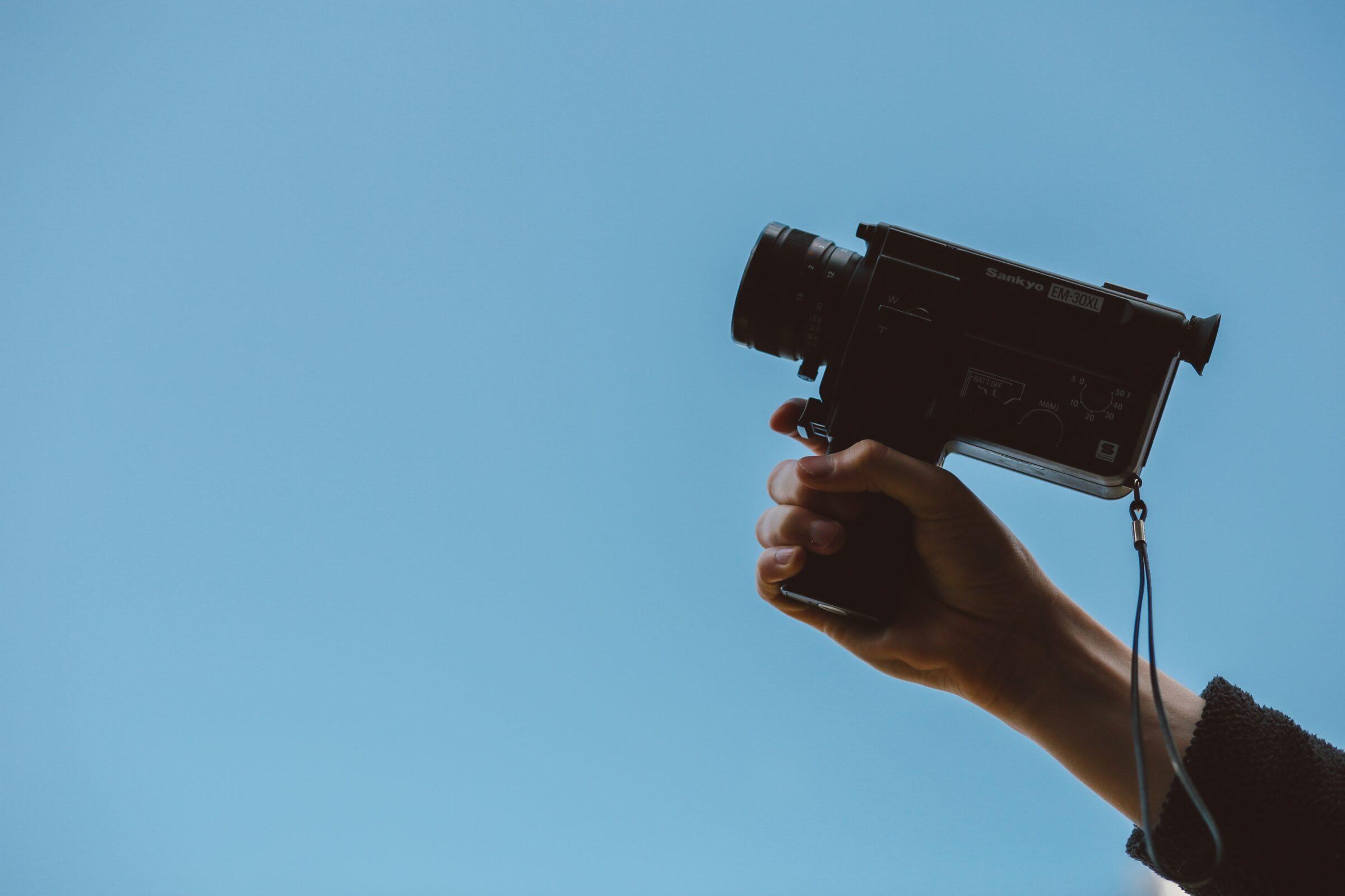 Hand houdt een camera in beeld met blauwe lucht op de achtergrond