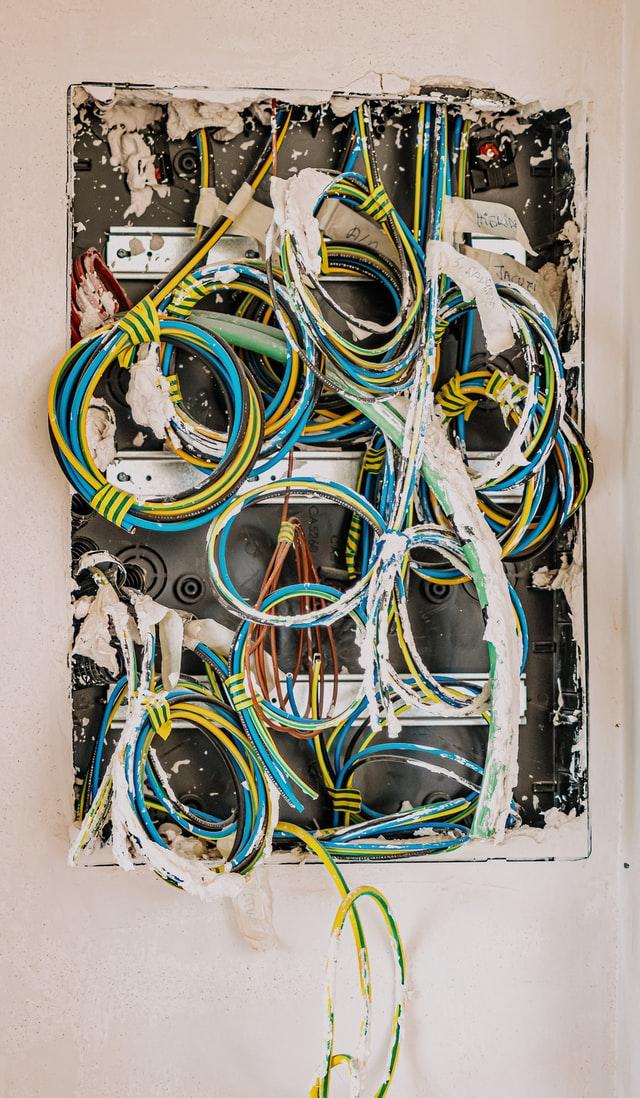 Foto van elektriciteitsdraden die uit een muur komen